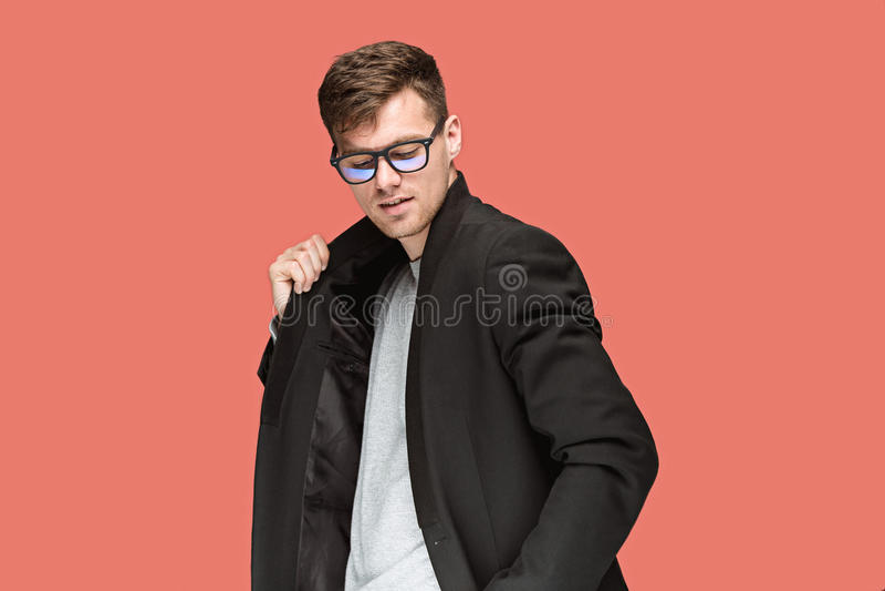Молодой красивый человек в черном костюме и стекла изолированные на красной предпосылке стоковое фото