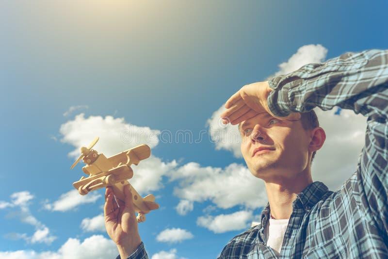Молодой красивый человек держа деревянный самолет в руке и смотря в расстояние Концепция фантазера стоковое фото