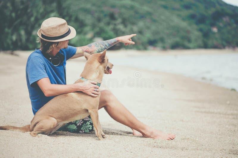Молодой красивый человек нося голубые футболку, шляпу и солнечные очки, сидя на пляже с собакой стоковые изображения rf