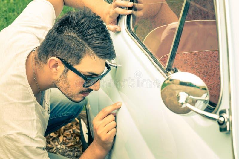 Молодой красивый человек при солнечные очки проверяя винтажное тело автомобиля стоковое изображение rf