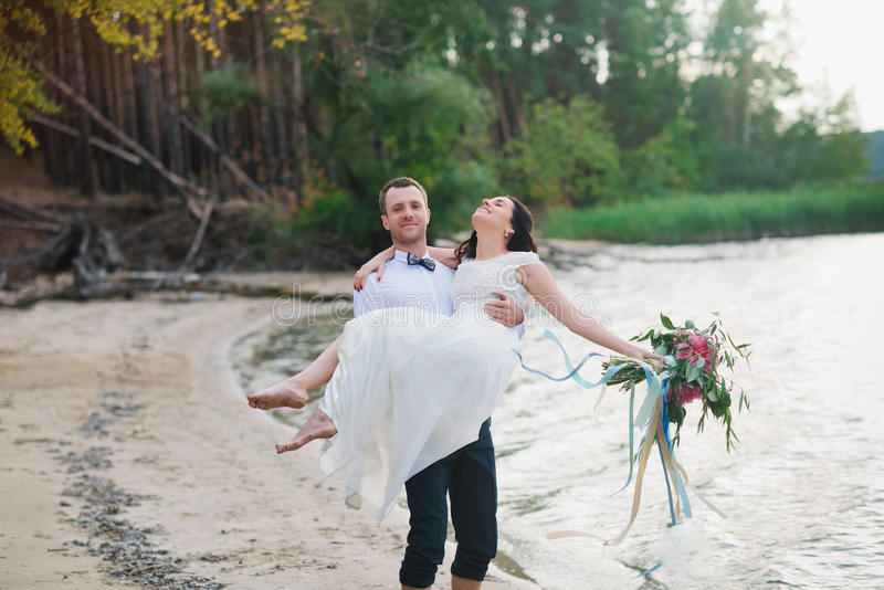 Молодой красивый groom держит его невесту в его оружиях на пляже с большим букетом красивых цветков стоковая фотография