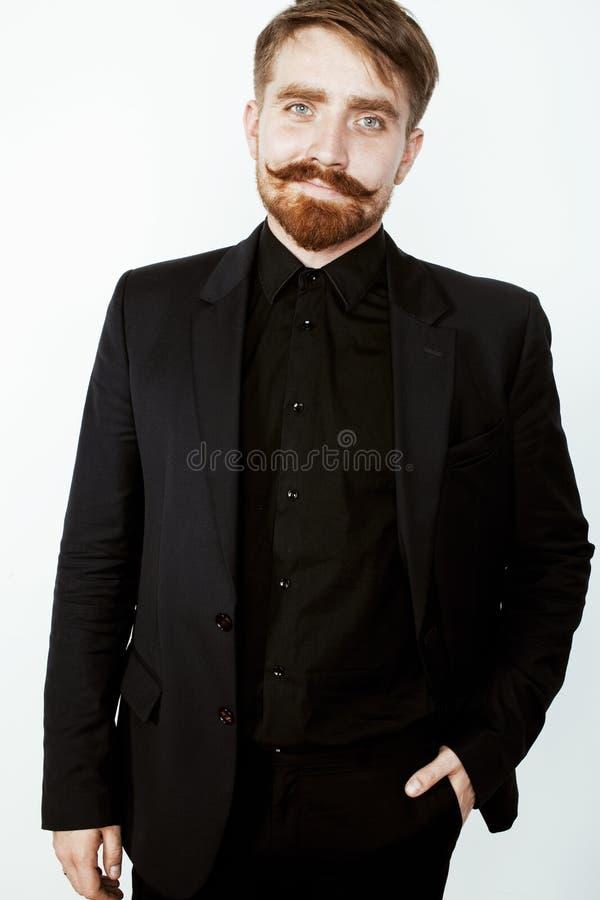 Молодой красный человек волос с бородой и усик в черном костюме на белой предпосылке стоковые изображения