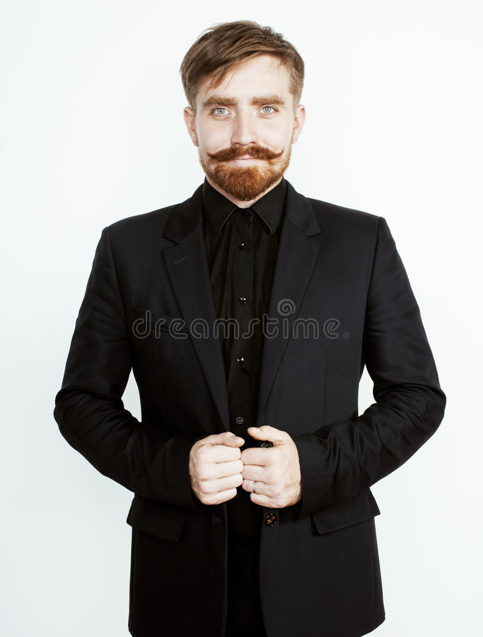 Молодой красный человек волос с бородой и усик в черном костюме на белой предпосылке стоковое фото