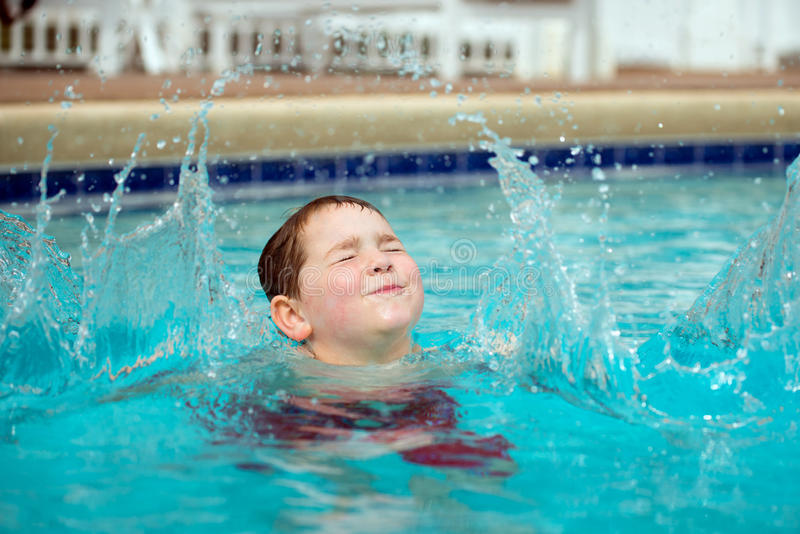 Молодой мальчик брызгая в бассейн стоковые фотографии rf