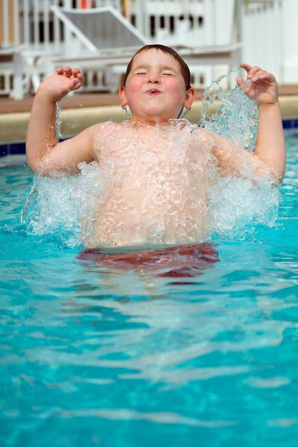 Молодой мальчик брызгая в бассейн стоковые фото