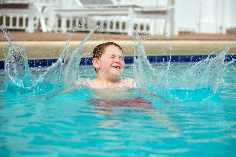 Молодой мальчик брызгая в бассейн стоковое изображение rf