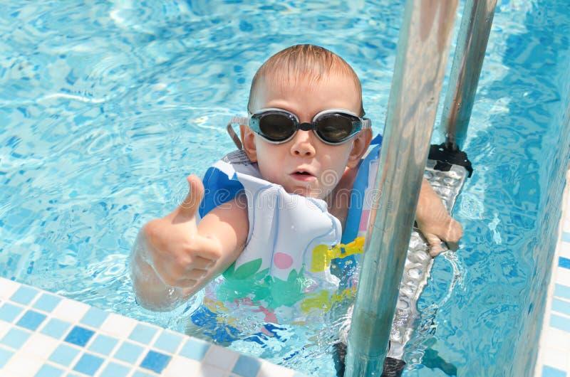 Молодой мальчик в давать бассейна большие пальцы руки вверх стоковое изображение rf