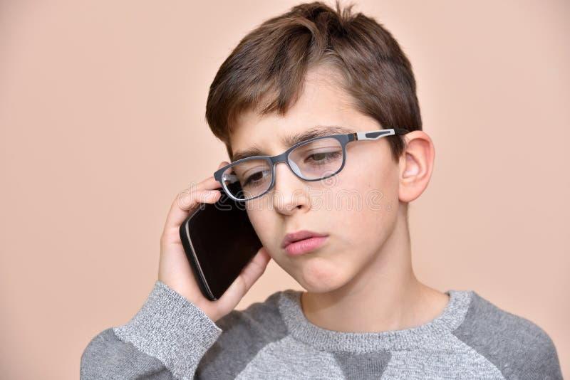 Молодой мальчик говоря на его умном телефоне стоковое изображение rf