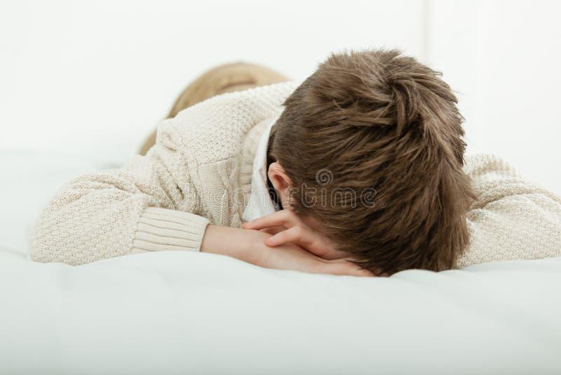 Молодой мальчик лежа на его кровати спать или плача стоковое фото rf