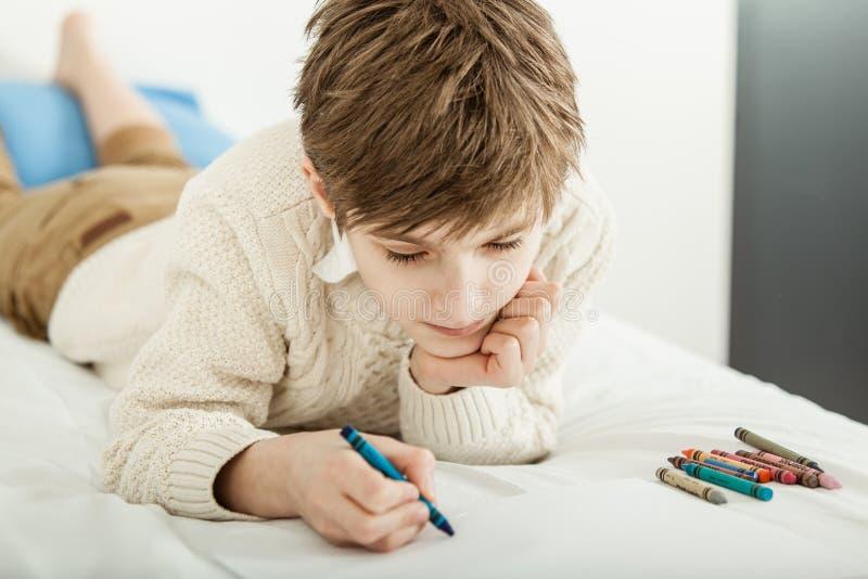 Молодой мальчик лежа на его чертеже кровати стоковые изображения rf