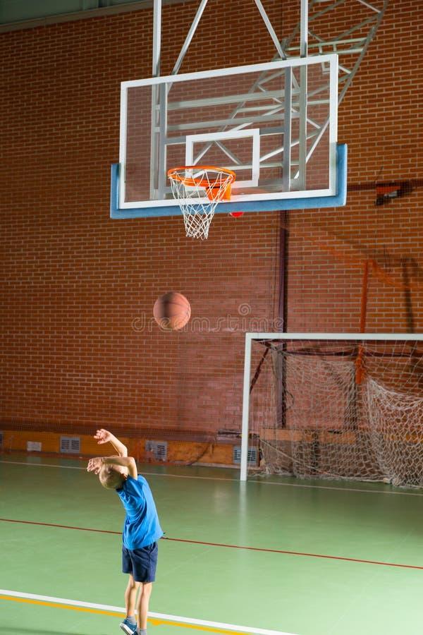 Молодой мальчик играя баскетбол внутри помещения стоковые изображения rf