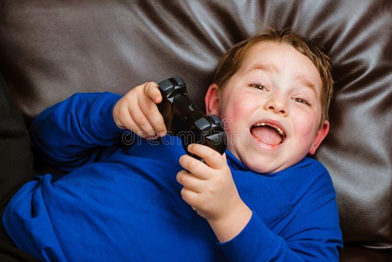 Молодой мальчик играя видеоигру кладя на кресло стоковое изображение