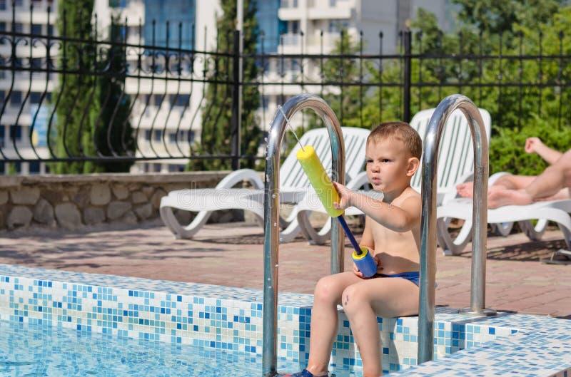Молодой мальчик играя в бассейне стоковое фото