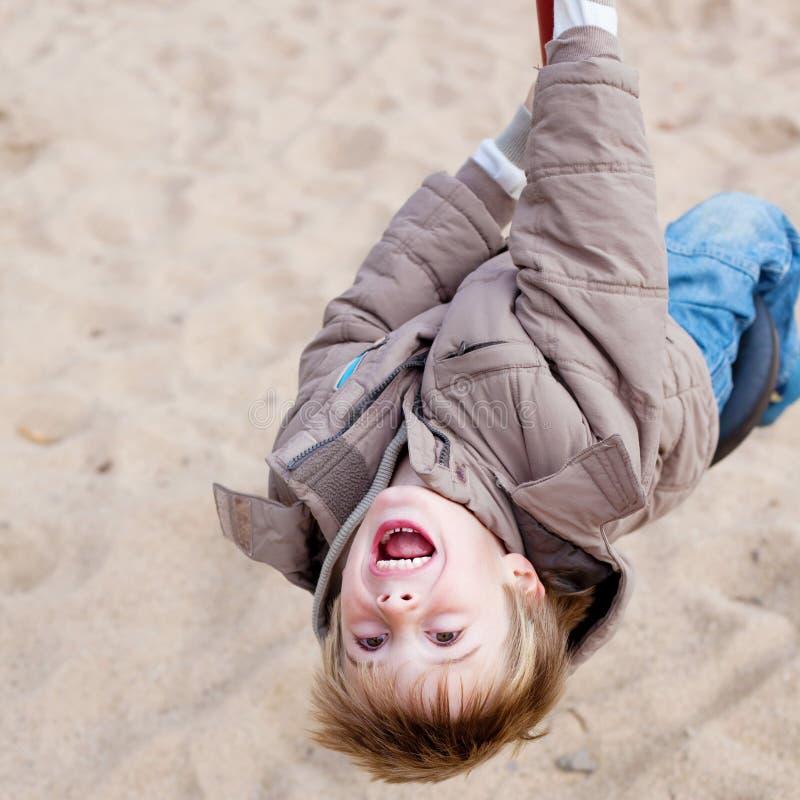 Молодой мальчик играя на спортивной площадке стоковое фото