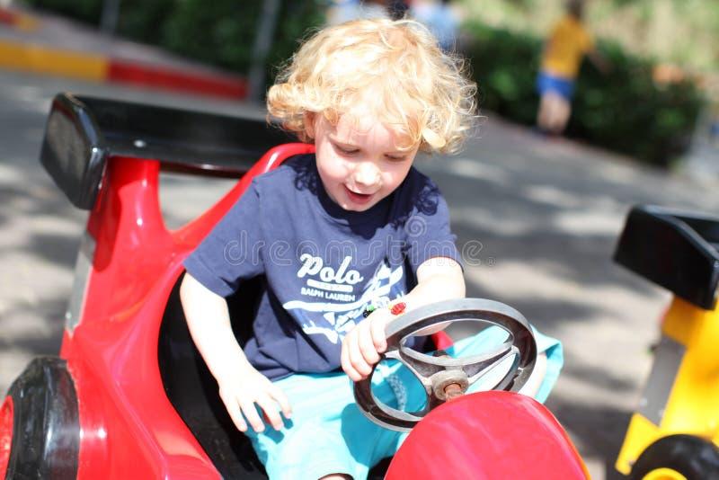 Молодой мальчик играя с автомобилем бампера стоковые фотографии rf