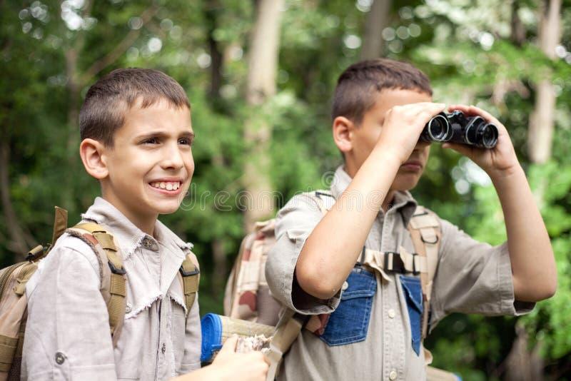 Молодой мальчик исследует природу с биноклями на походе стоковая фотография rf