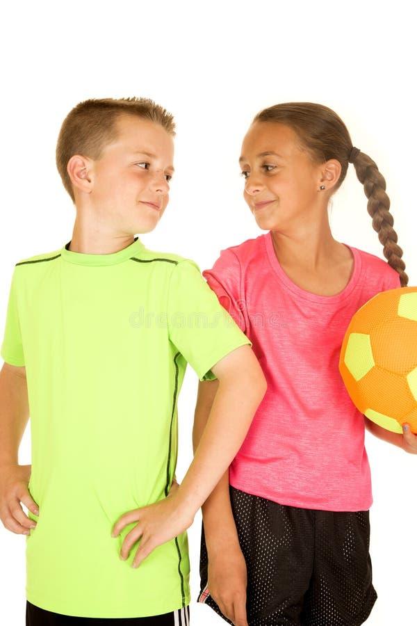 Молодой мальчик и девушка держа футбольный мяч с ориентацией стоковые изображения rf
