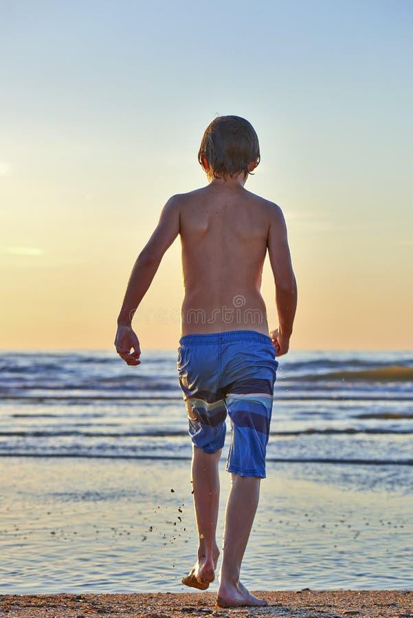 Молодой мальчик идет поплавать в волнах стоковая фотография