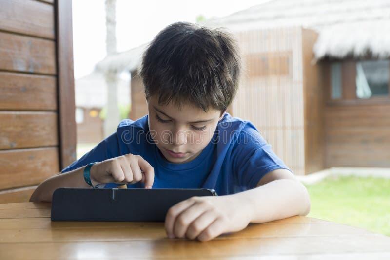 Молодой мальчик и таблетка цифровая стоковое изображение rf