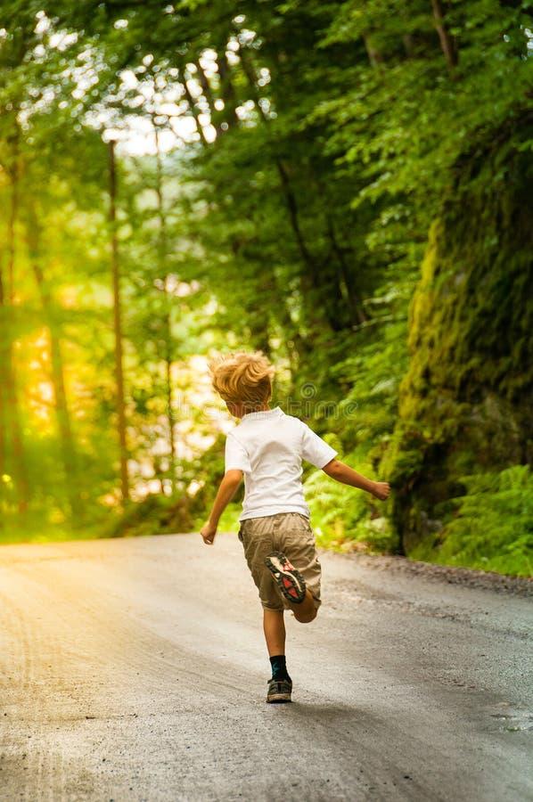 Молодой мальчик, который побежали в лесе стоковые фото