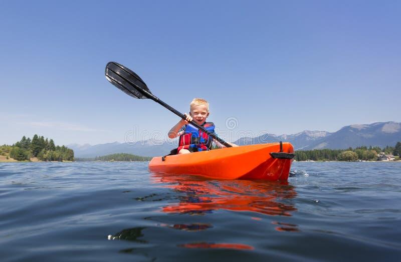 Молодой мальчик полоща каяк на красивом озере горы стоковые фотографии rf