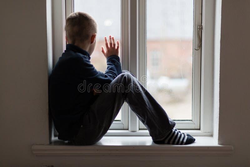Молодой мальчик сидя на развевать windowsill стоковые изображения rf
