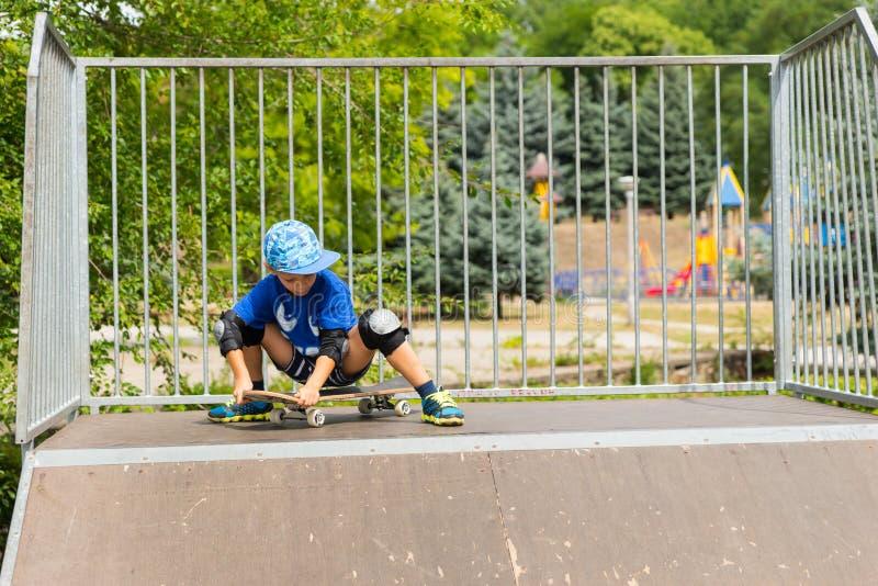 Молодой мальчик сидя на скейтборде наверху пандуса стоковое изображение rf