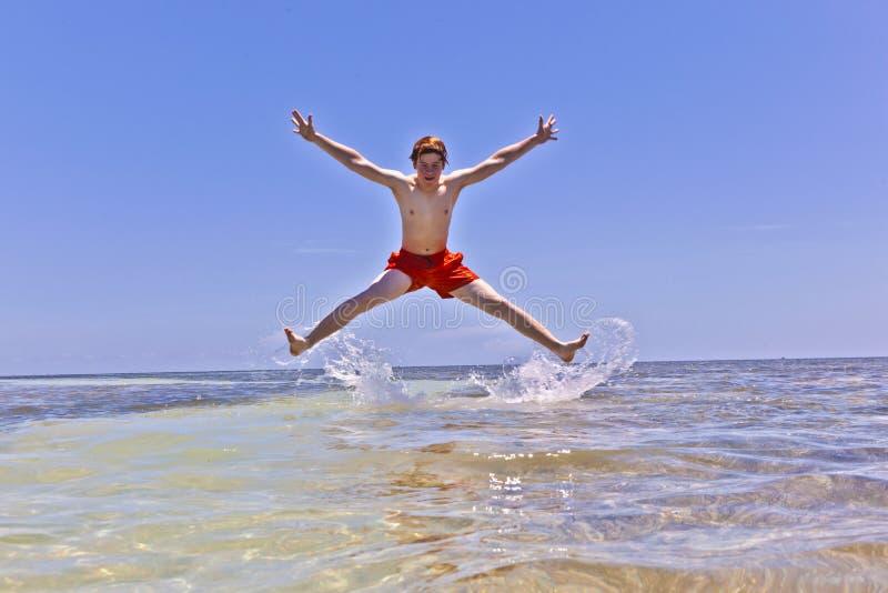 Молодой мальчик скача из воды стоковая фотография rf