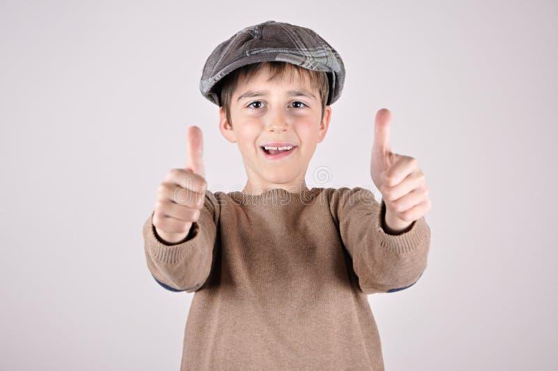 Молодой мальчик с большими пальцами руки вверх стоковое фото rf