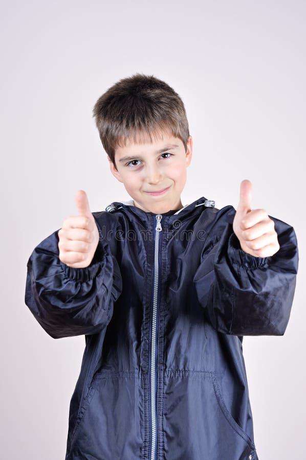 Молодой мальчик с большими пальцами руки вверх стоковое изображение