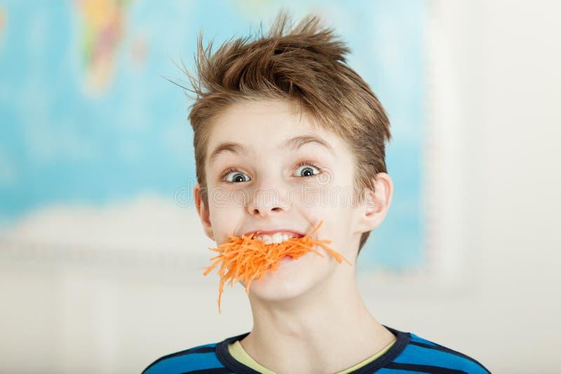 Молодой мальчик с его рот вполне заскрежетанной моркови стоковые изображения