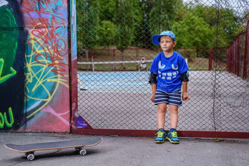 Молодой мальчик с его скейтбордом на теннисном корте стоковая фотография