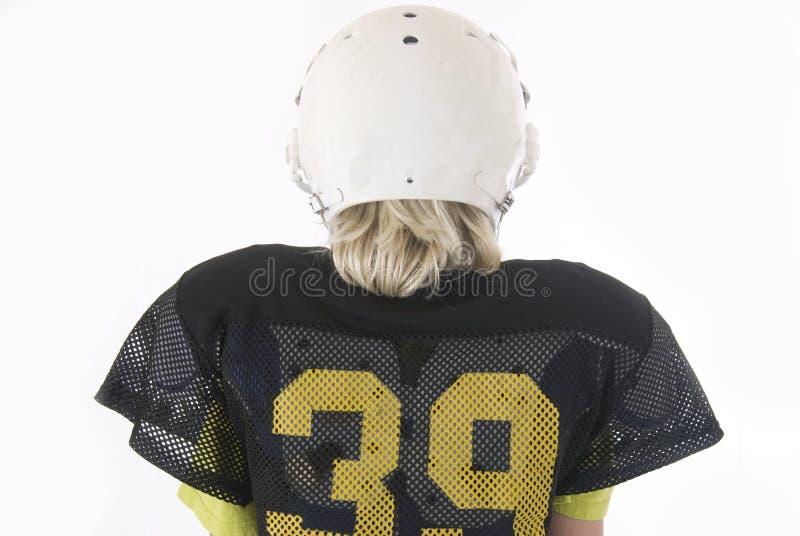 Молодой мальчик с длинними белокурыми волосами в форме американского футбола стоковая фотография rf