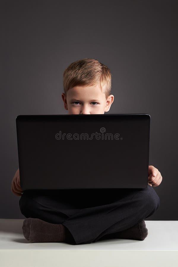 Молодой мальчик с компьютером смешной ребенок смотря в тетради стоковое фото