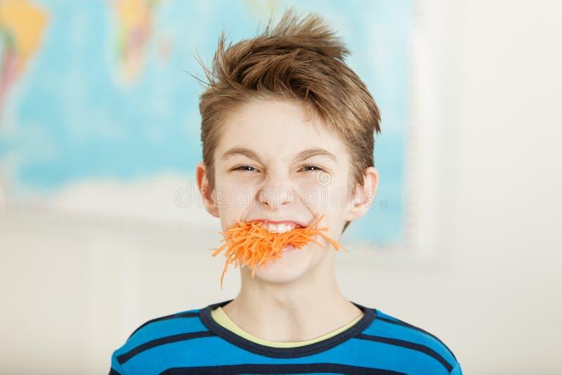 Молодой мальчик с полным ртом заскрежетанной моркови стоковые фото
