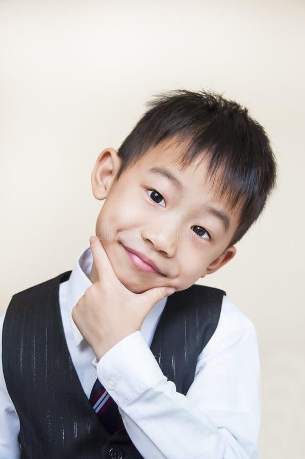 Молодой мальчик с руками на подбородке стоковые изображения rf