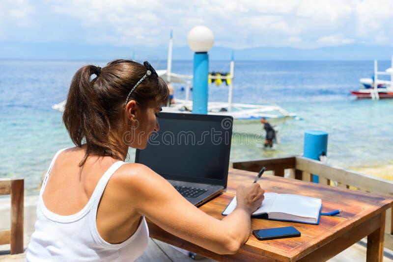 Молодой милый писатель фрилансера женщины работая с блокнотом компьтер-книжки и телефоном перед голубым тропическим морем стоковое фото rf