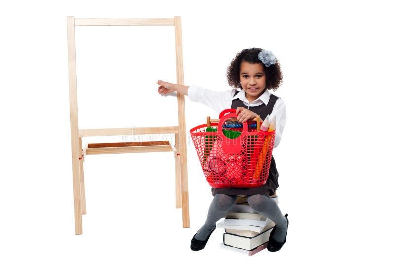 Молодой милый ребенк сидя на куче книг стоковое изображение rf