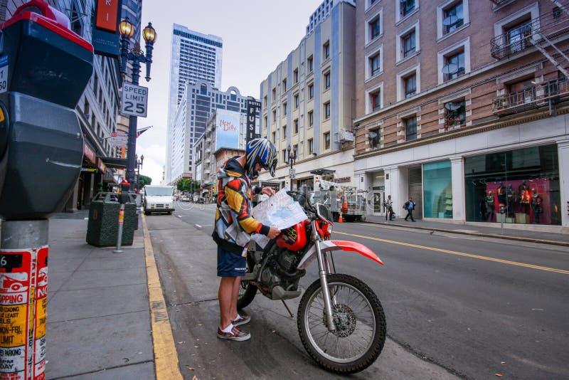 Молодой мотоциклист проверяя направления на карте на улице города стоковое фото rf