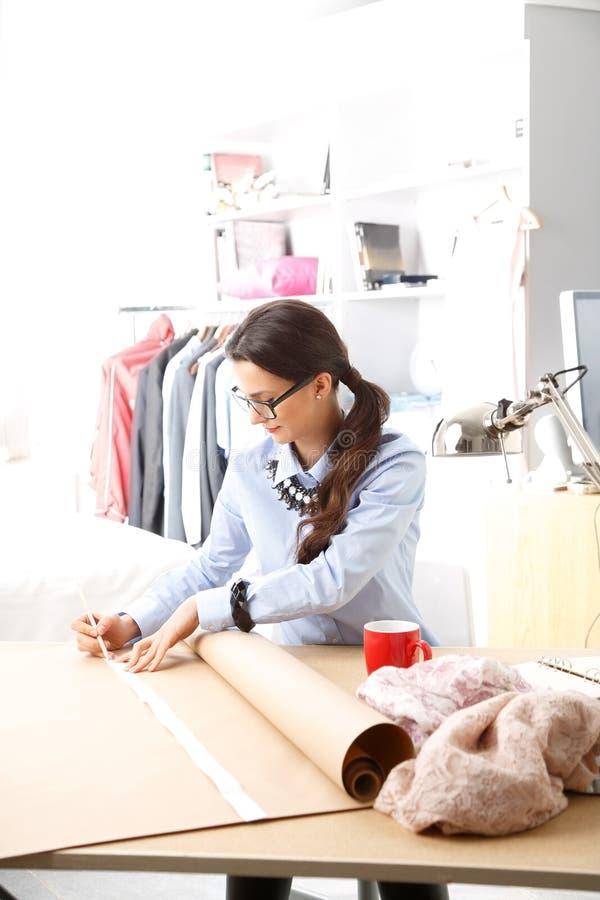 Молодой модельер работая в ее студии стоковое фото rf
