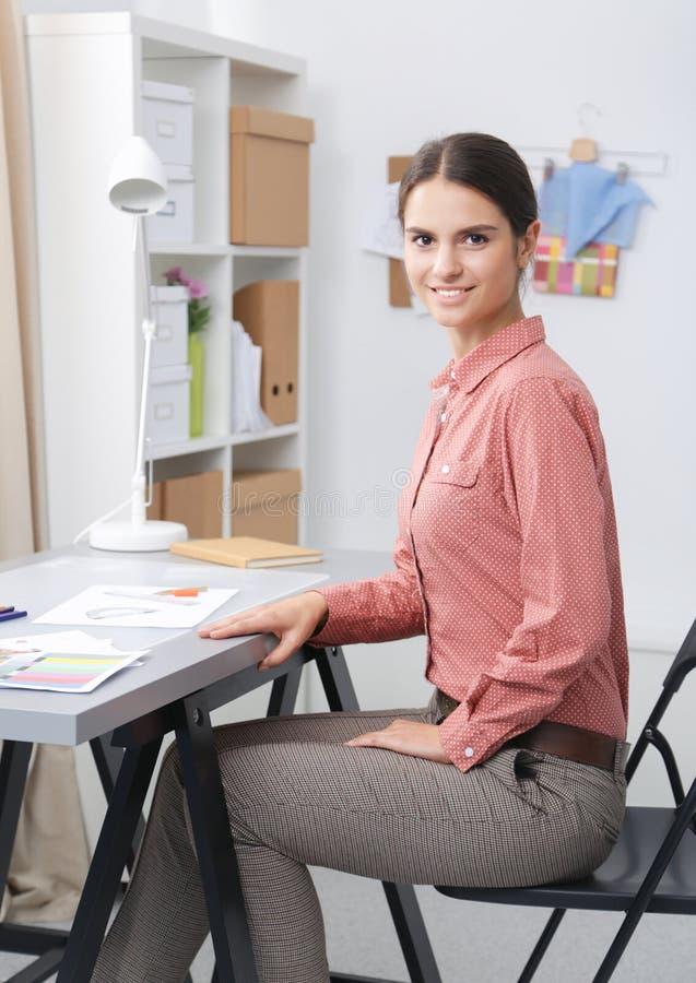 Молодой модельер работая на студии стоковое фото