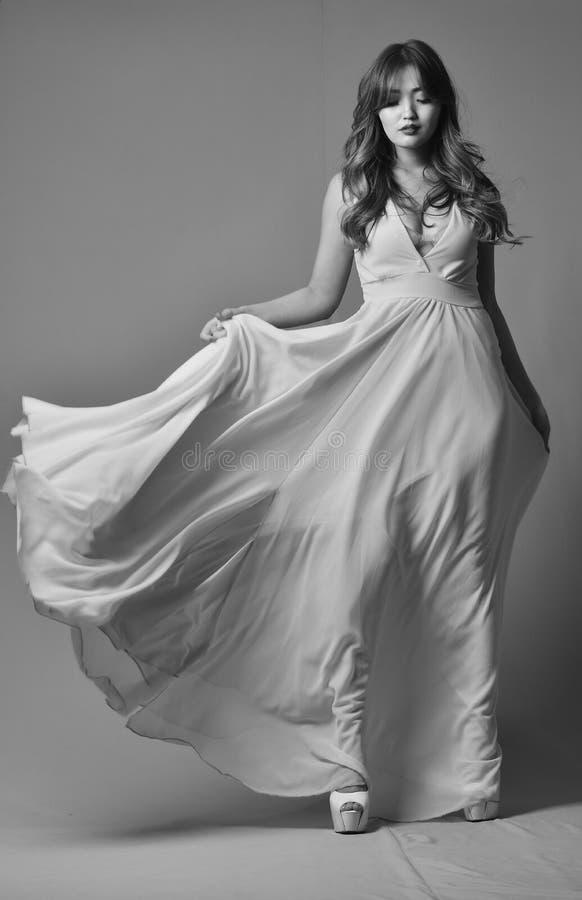 Молодой модельный представлять в элегантном длинном платье порхая в ветре Черн-белое фото стоковое изображение