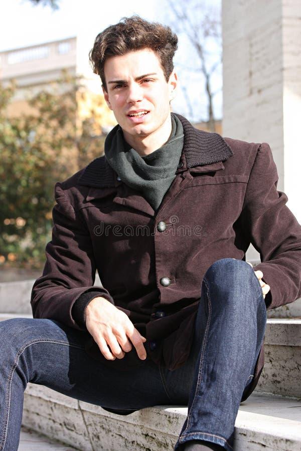 Молодой модельный человек сидя на мраморных шагах стоковые фотографии rf