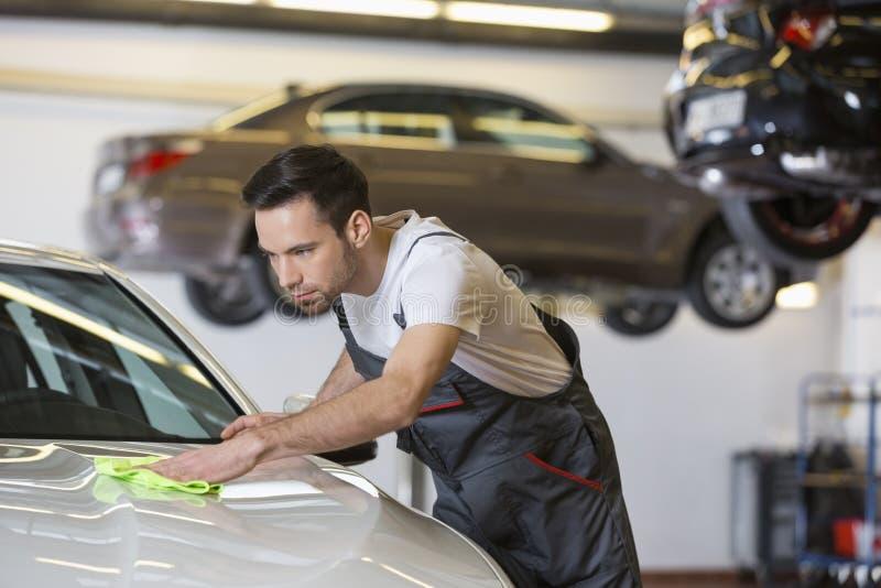 Молодой мужской автомобиль чистки механика в ремонтной мастерской стоковая фотография rf
