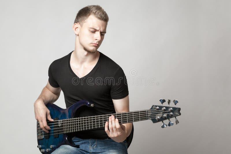 Молодой мужской музыкант играя изолированную гитару 6-строки басовую стоковые изображения rf