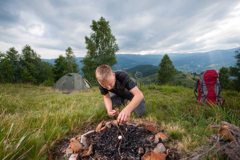 Молодой мужской hiker разжигать швырок на холме с шатром стоковые изображения rf