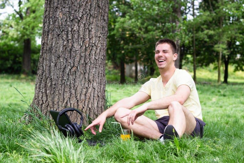 Молодой мужчина используя компьтер-книжку в парке стоковые изображения