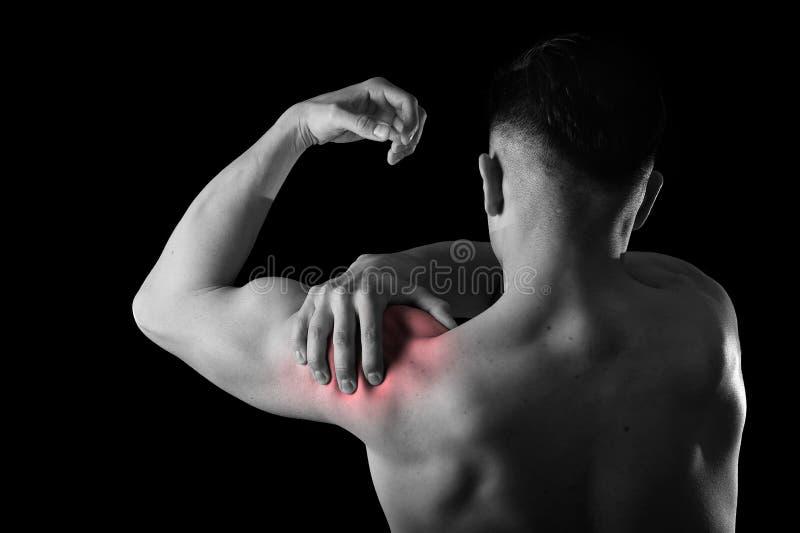 Молодой мышечный человек спорта держа больное плечо в боли касаясь массажировать в стрессе разминки стоковое фото rf