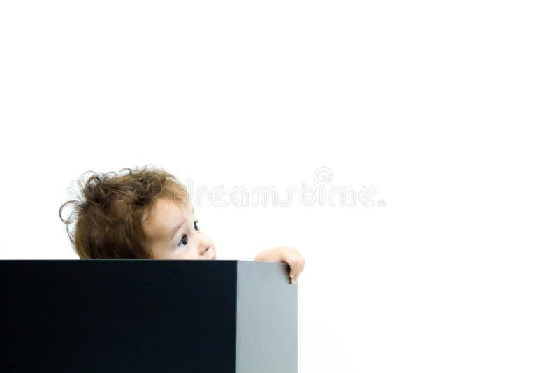 Молодой младенческий мальчик peeking из коробки на белой предпосылке стоковые изображения
