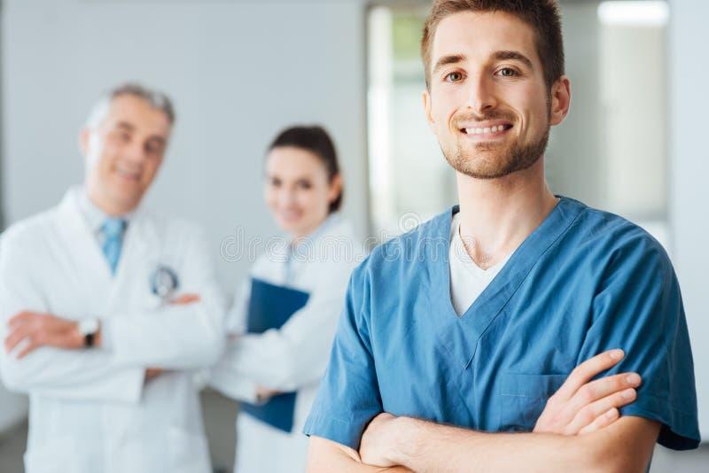 Молодой доктор представляя и усмехаясь на камере стоковое изображение rf